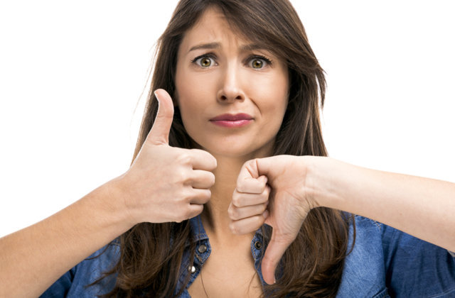 Beautiful woman confused making thumbs up and down